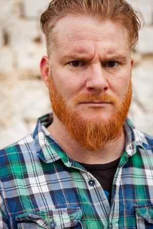 Portrait of red haired hipster man with blue plaid shirt expressing a emotion Stock Photo