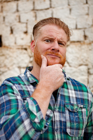 Pensive red haired hipster man with blue plaid shirt in a rural enviroment Stock Photo