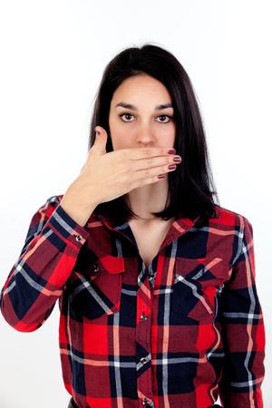 Morena joven que cubre su boca aislada en un fondo blanco Foto de archivo