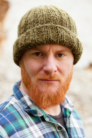 Red haired man with blue plaid shirt and wool hat
