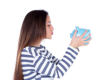 Teenager girl with blue piggy bank isolated on a white background photo