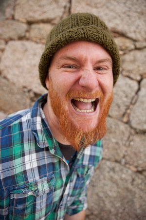 Portrait of a red haired hipster guy putting silly face
