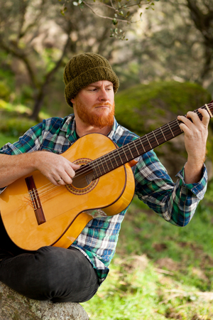 Hipster man with red beard playing a guitar in the field Stock Photo
