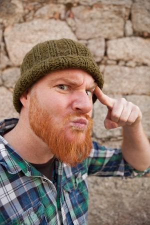 expressive face: Portrait of a red haired hipster guy putting silly face  Stock Photo