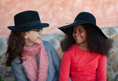 Two happy girls friends with stylish hats lauging photo