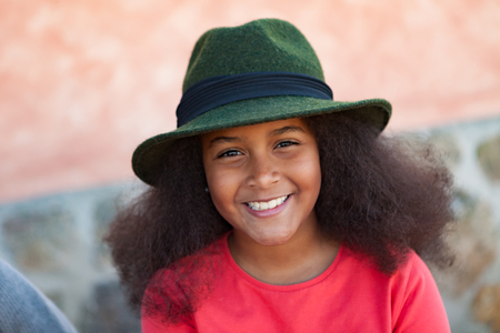 Pretty girl with long afro hair in the garden with a elegant black hat photo