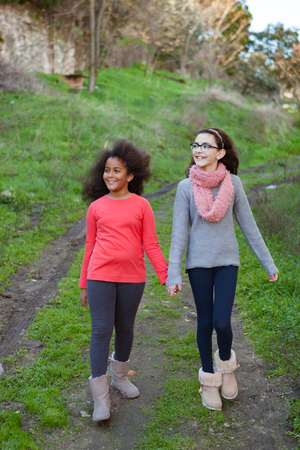 Two beautiful girls taking a walk by a green field Stock Photo