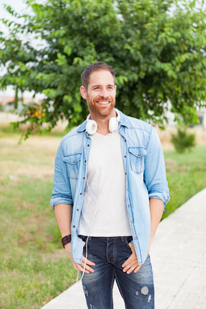earbud: Casual guy with white headphones is taking a walk in the park in his free time