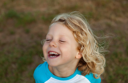 Small child with long blond hair enjoying of a sunny day 免版税图像