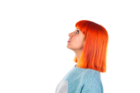 Attractive profile of a redhead girl looking up isolated on a white background