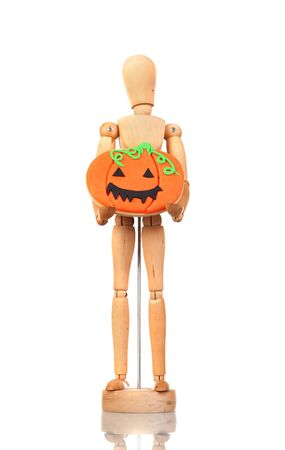 Wooden articulated doll holding a pumpkin cookie on the white isolated background