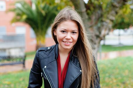 misterious: Blonde woman with leather jacket in a park