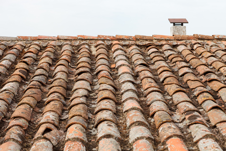damaged roof: Broken brick on the roof of a cottage. Damaged roof. Stock Photo