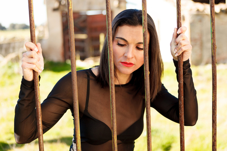 Attractive woman behide the bars with red lips