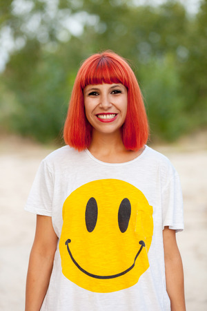 Portrait of red haired woman with a funny shirt in a park