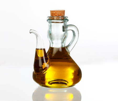 Oil bottle with the golden juice of the olive isolated on white background Banco de Imagens - 93555973