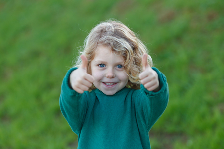 Adorable small blond child saying Ok in a park Фото со стока
