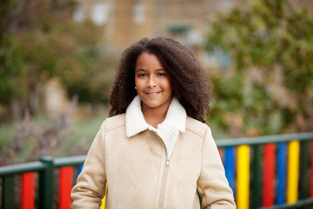 African girl with a beautiful hair in a park