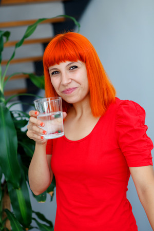 Happy woman drinking a glass of water at home Stock Photo