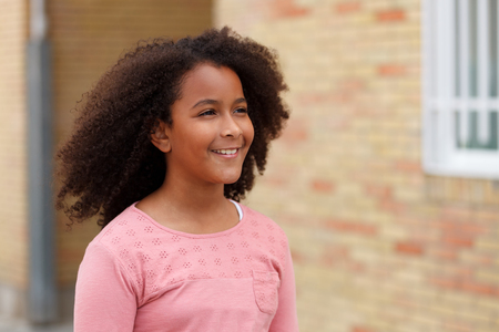 Cute African American girl smiling in the street with afro hair Banque d'images