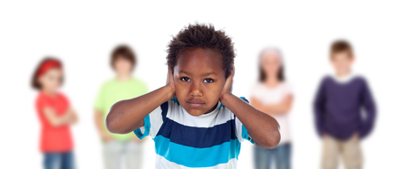 Afro-American child frightened covering his ears ang blurry children of background Foto de archivo - 97558983