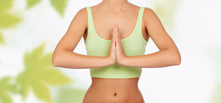 Anonymous woman doing yoga with green leaves of background