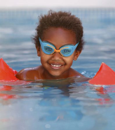 Little african child with orange sleeve floats in the pool Reklamní fotografie