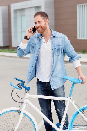 Casual guy next to a vintage bicycle with the mobile wearing denim shirt Stockfoto