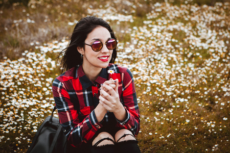 Beautiful woman with sunglasses sitting in the middle of a flowery meadow smelling a daisy