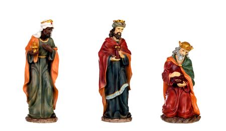 Los tres reyes magos y el niño Jesús. Figuras de cerámica aisladas sobre fondo blanco. Foto de archivo