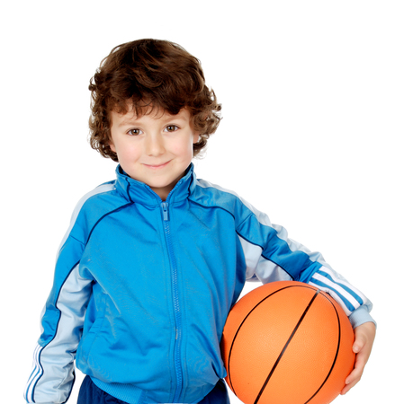 Chico divertido con chándal azul sosteniendo una pelota de baloncesto