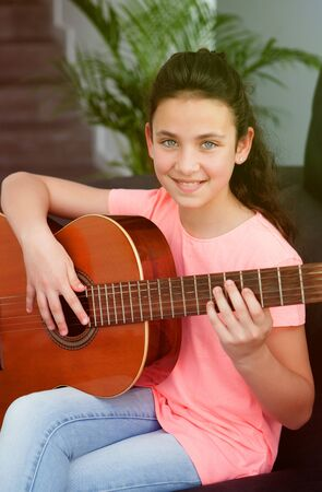 Young girl playing guitar on the sofa at home Stok Fotoğraf