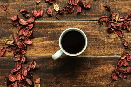 Coffe cup with red dry petals on a wooden background Banque d'images - 133514451