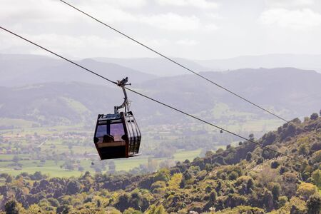 Cable car flying on the mountain. A funny transport Stock Photo