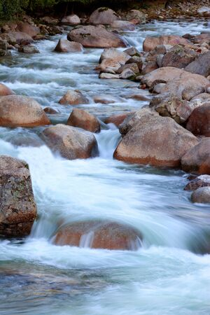 Beautiful river and big rocks with moss in autumn