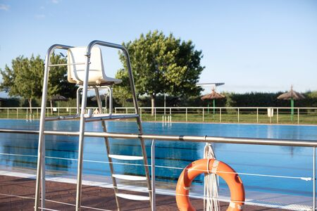 Orange lifebuoy floating on the surface of blue water in a pool