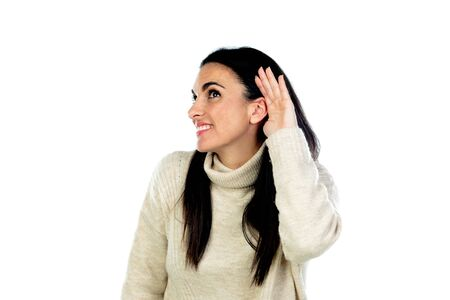 Attractive brunette woman listening something isolated on a white background