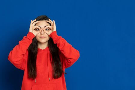 Brunette young girl wearing red jersey on a blue background Banque d'images