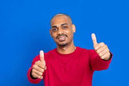 African man with red T-shirt on a blue background