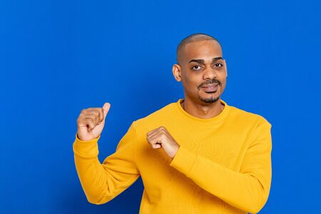 African guy with a yellow jersey on a blue background Stok Fotoğraf