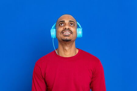 African man with red T-shirt on a blue background 版權商用圖片