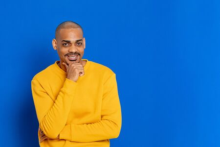 African guy with yellow jersey on a blue background