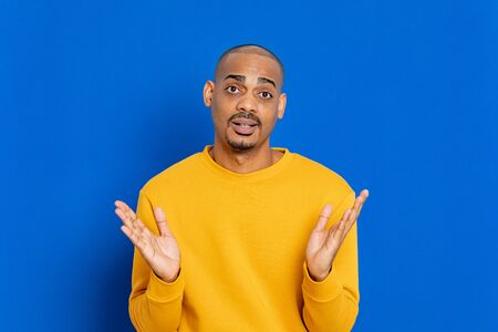 African guy with a yellow jersey on a blue background Stock Photo