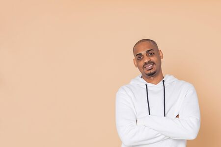 African guy wearing a white sweatshirt on a orange background