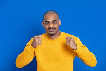 African guy with a yellow jersey on a blue background