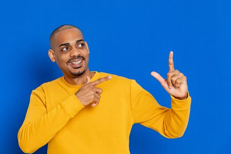 African guy with a yellow jersey on a blue background 版權商用圖片