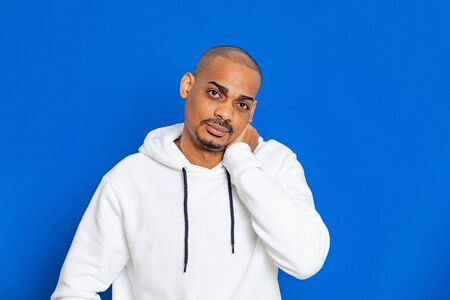 African guy wearing a white sweatshirt on a blue background