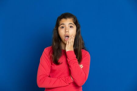 Adorable preteen girl with red t-shirt on a blue background