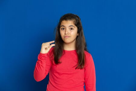 Adorable preteen girl with red t-shirt i on a blue background Foto de archivo
