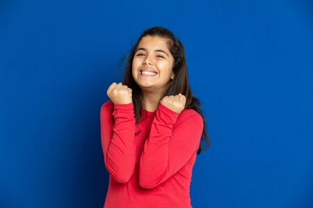 Adorable preteen girl with red t-shirt i on a blue background